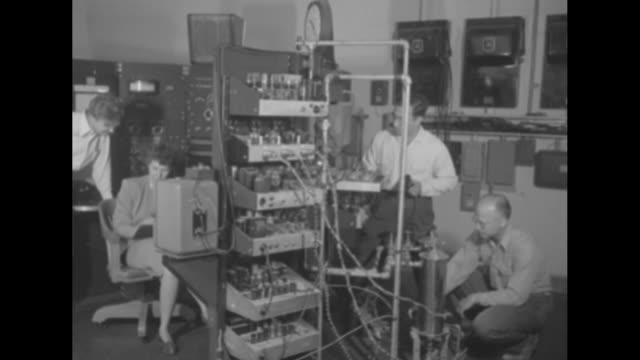 scientist making adjustment to valves / hand reaches up and pushes button on control panel / scientists in room working on electronic equipment zoom... - atomic bomb stock videos & royalty-free footage