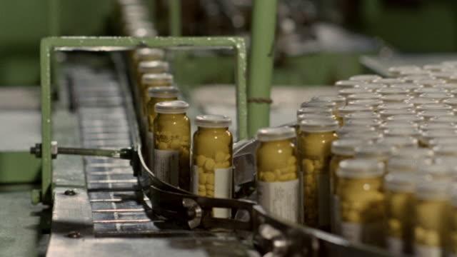 vidéos et rushes de 1968 montage scientist measuring liquids and medication bottles rolling through a factory assembly line / united kingdom - chaîne de production