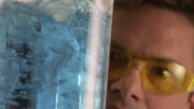 vidéos et rushes de cu, scientist observing blue liquid bubbling in lab flask, atlanta, georgia, usa - tube à essai