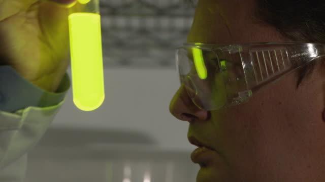 CU, Scientist observing fluorescent liquid in test tube, Atlanta, Georgia, USA