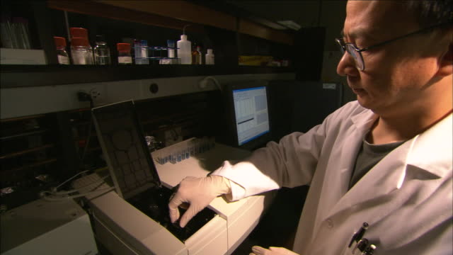 a scientist places samples into a machine. - latex stock videos & royalty-free footage
