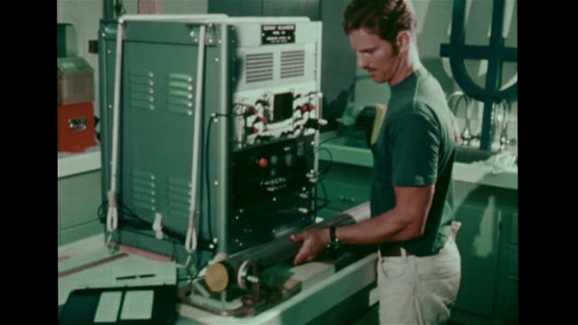 Scientist placing glass tube holding ocean floor samples onto equipment adjusting dials writing notes CU Waveform on monitor Oceanography scientific...