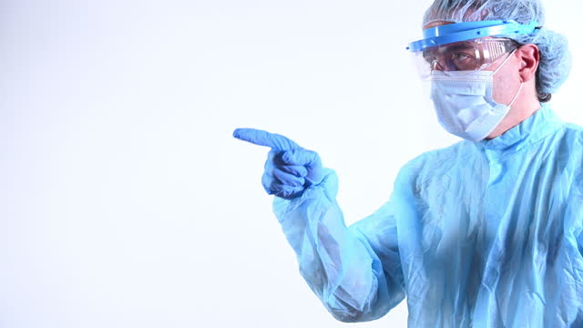 scientist pointing with his index finger in one direction. he is wearing a mask, gloves and glasses and protective suit - index finger stock videos & royalty-free footage