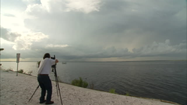 a scientist points a measuring device towards gray storm clouds hanging over a river. - measuring stock videos & royalty-free footage