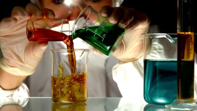 wissenschaftler gießen und mischen chemikalien in becherglas - becherglas stock-videos und b-roll-filmmaterial