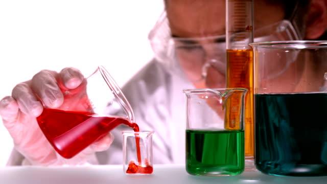 科学者注ぐレッドの液体をビーカー - ビーカー点の映像素材/bロール