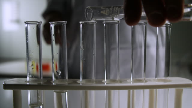 scientist pours clear liquid into test tube - analysing stock-videos und b-roll-filmmaterial