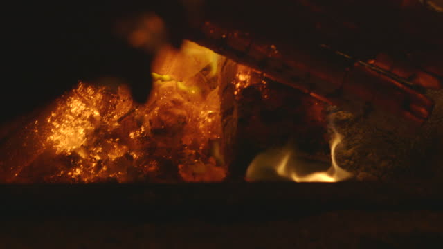 Scientist pours powdered chemicals onto a fire