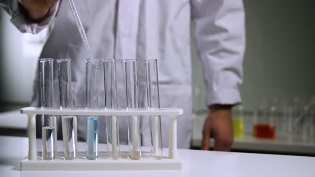 vidéos et rushes de scientist puts blue liquid in test tube - tube à essai