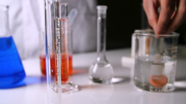 scientist puts effervescent tablet in beaker - laboratory coat stock videos & royalty-free footage
