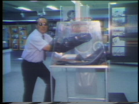 scientist reaches into an airtight containment unit using attached rubber gloves. - 密閉点の映像素材/bロール