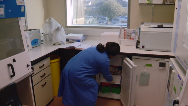 a scientist removes samples from a freezer whilst researching mers vaccines at the clinical biomanufacturing facility in oxford - adults only stock videos & royalty-free footage