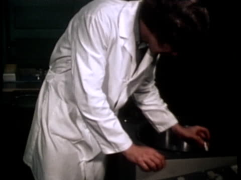 vidéos et rushes de 1976 montage ms cu scientist removing test tube and showing it to camera / united states / audio - blouse de laborantin