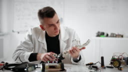 Scientist researcher constructing and testing robotic hand prosthesis at table