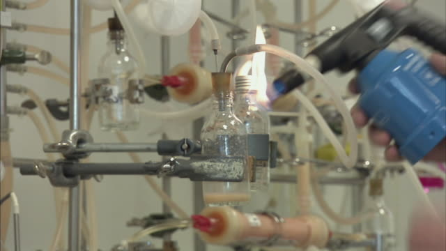 cu scientist sanitizing vials and test tubes with fire for chemistry experiment, boxmeer, netherlands - boxmeer video stock e b–roll