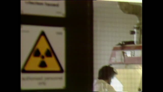 scientist sitting at specially protected apparatus testing for aids, pan up to infection hazard sign, uk; 1987. - risk stock videos & royalty-free footage