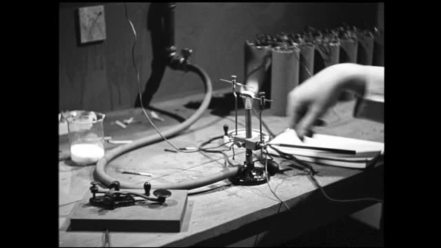 scientist sitting in front of table, writes something on notebook, experimenting with telegraph, earpiece, and bunsen burner - 1940 1949 stock videos & royalty-free footage
