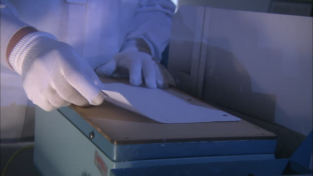 a scientist stretches transparent plastic over a document in a forensics lab. - forensic science stock videos & royalty-free footage