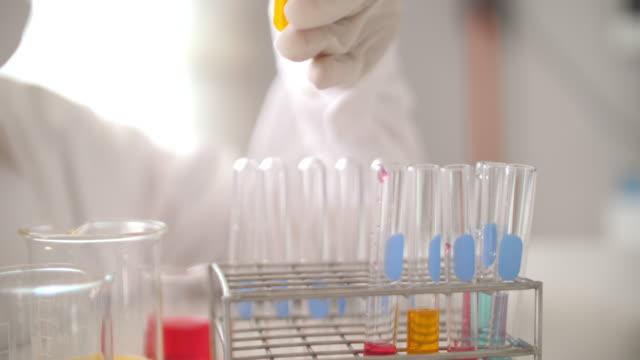 soluzioni di test per scienziati in laboratorio - vetreria da laboratorio video stock e b–roll