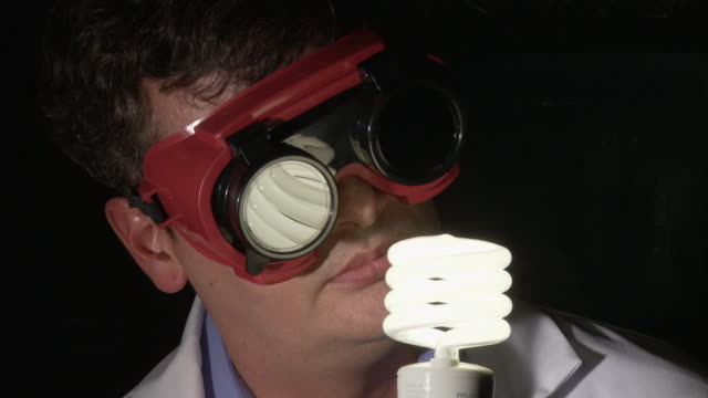 cu, scientist turning on and observing energy efficient light bulb wearing protective goggles, atlanta, georgia, usa - energy efficient lightbulb stock videos and b-roll footage