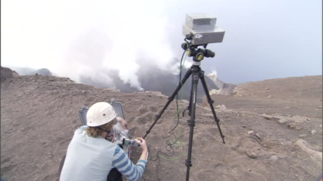 a scientist uses equipment on a tripod to collect data from a nearby volcano. - geology stock videos & royalty-free footage