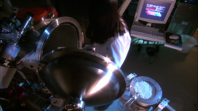 a scientist uses equipment to simulate asteroid materials in a lab. - astronomie stock-videos und b-roll-filmmaterial