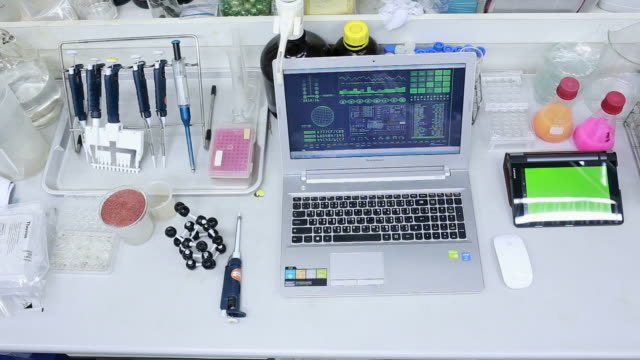Scientist using computer, microscope and molecule model.