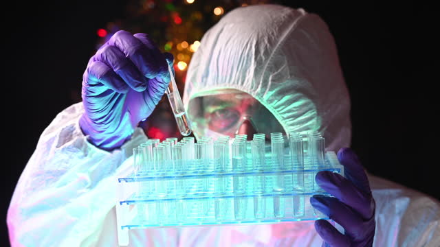 scientist very concentrated in his work catching a a test tube with liquid inside. there is a decorated christmas tree in the background. - group of objects stock videos & royalty-free footage