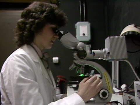 A scientist views a slide through a microscope in a laboratory