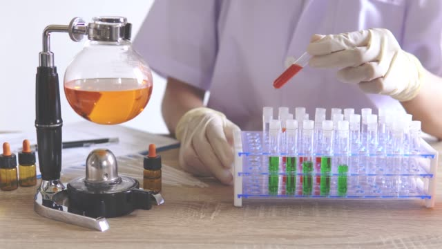 scientist with equipment and adding liquid to test-tubes for science experiments  in a laboratory. healthcare and biotechnology concept. - only mid adult women stock videos and b-roll footage