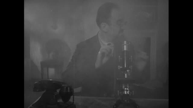 MONTAGE Scientist with microscope in smoke-filled room, apparition telling him to call the fire department, hand dialing rotary phone, and ladder and fireman appearing at window / United Kingdom