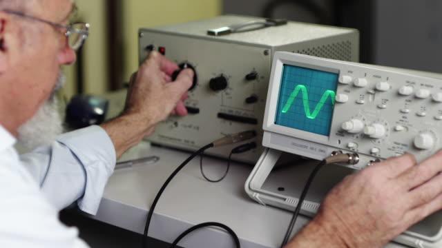 vídeos de stock e filmes b-roll de cientista com osciloscópio - equipamento elétrico equipamento de recreio
