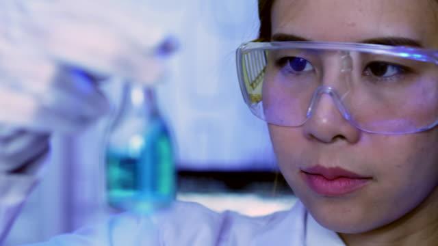 vidéos et rushes de femme scientifique dans un laboratoire - formule chimique