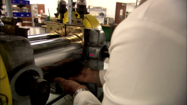 a scientist works a fat piece of a rubber-like material through rollers. - rubber stock videos & royalty-free footage