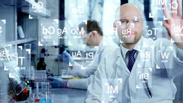 vídeos de stock e filmes b-roll de cientistas analisar a tabela periódica de elementos - combinação química