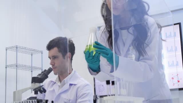 vídeos y material grabado en eventos de stock de los científicos están determinadas actividades en la ciencia experimental como mezclar productos químicos o los datos de entrada para el desarrollo de la medicina, alimentos para todos en el mundo - química