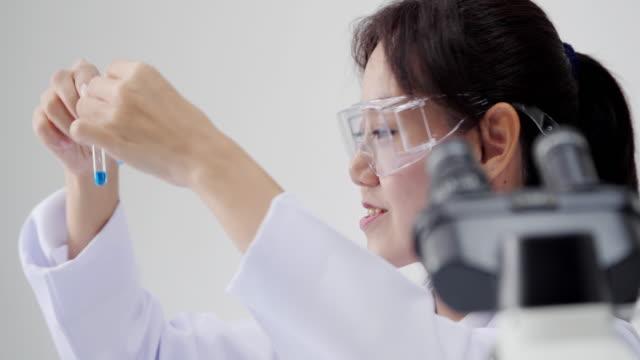 gli scienziati sono alcune attività sulla scienza sperimentale come la miscelazione di sostanze chimiche o i dati di ingresso per sviluppare la medicina - vetreria da laboratorio video stock e b–roll