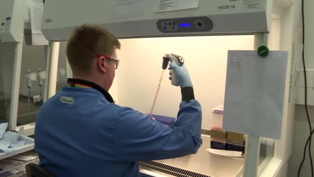 scientists at oxford university developing new ebola vaccine england int scientists sitting at laboratory desk with vaccines / close shot of test... - development stock videos & royalty-free footage