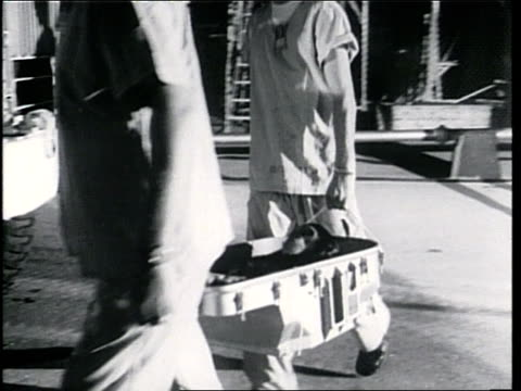 scientists carry a chimpanzee strapped in a space capsule to a truck - anno 1961 video stock e b–roll