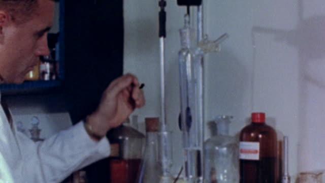 vídeos y material grabado en eventos de stock de ws scientists carrying  out various experiments in science lab / united states - 1960