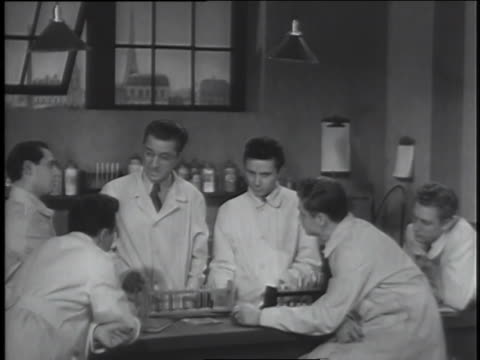 """scientists confer while a teacher speaks about their accomplishments in a classroom; a speaker talks about the superiority of fascist scientists and the need to wipe out """"inferior"""" races. - military uniform stock videos & royalty-free footage"""