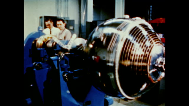 / scientists designing rocket engines to be used with new atmospheric explorers in space / instruments shown that will be carried aboard satellite... - 製図板点の映像素材/bロール