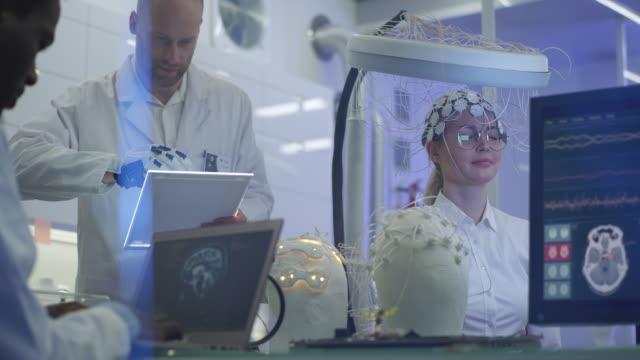 scientists examining brainwave scanning headset in laboratory. - human brain stock videos & royalty-free footage