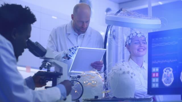 scientists examining brainwave scanning headset in laboratory. - neuroscience stock videos & royalty-free footage