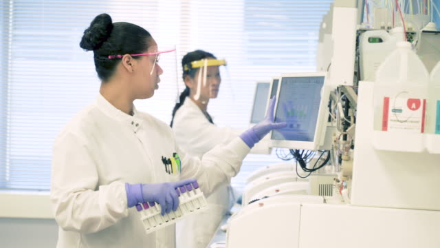 scientists in bio-medical laboratory operating blood analysis equipment - microbiology stock videos and b-roll footage