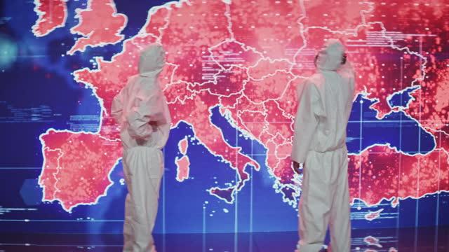 vidéos et rushes de des scientifiques en costume propre. carte d'infection de la projection de l'europe. une très grande infectiosité - représentation féminine