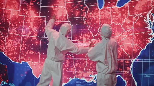 vidéos et rushes de des scientifiques en costume propre. carte d'infection de la projection des usa. une très grande infectiosité - représentation féminine