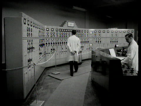scientists in front of control panel at rye house nuclear power station hertfordshire 1950s - ハートフォードシャー点の映像素材/bロール