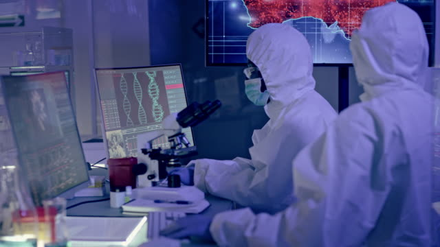 scientists in futuristic laboratory working with biohazardous substance. looking at screen with australia outbreaks - biology stock videos & royalty-free footage