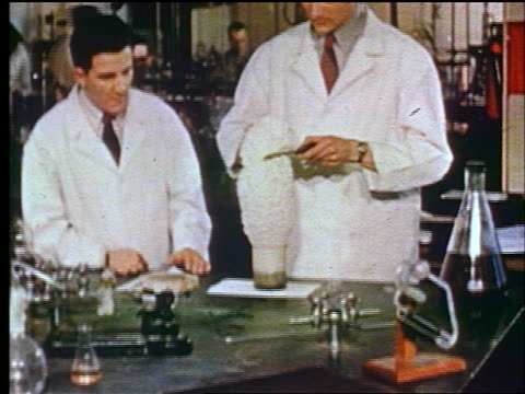 1947 2 scientists in laboratory pulling steaming polystyrene from beaker / educational